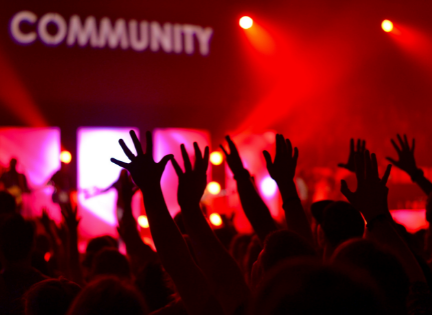 audience reaching towards a community sign